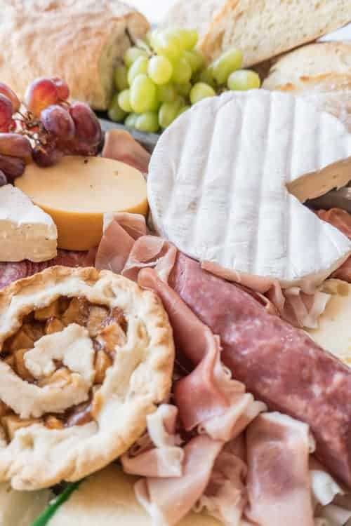 Charcuterie Board,This meat and cheese board is filled with so many delicious items and it's not just limited to meat and cheese! Fruit, mini pies and even some bread go perfectly with this delicious tray of goodies! #atablefullofjoy #cheese #charcuterie #bread #yummy