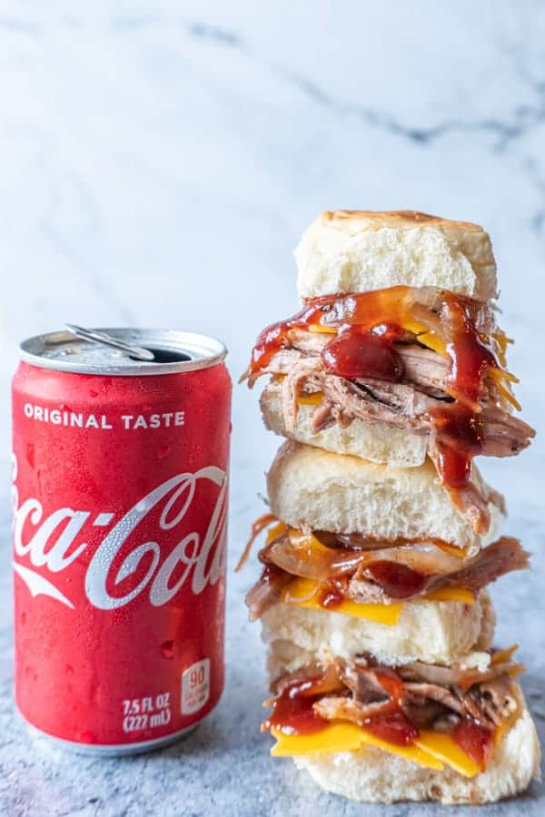 Coca-Cola Pulled Pork Sliders stacked on one another next to a can of coke.