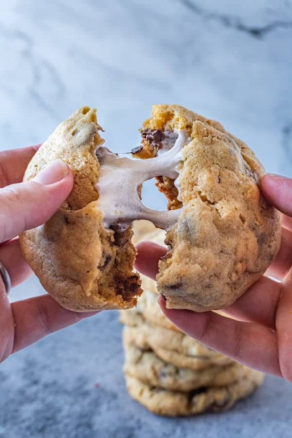 S'mores Stuffed Cookies being pulled apart with gooey marshmallow in center