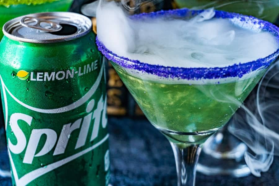 Bright Shimmery Green Drink next to Sprite Can with dry ice smoke on top