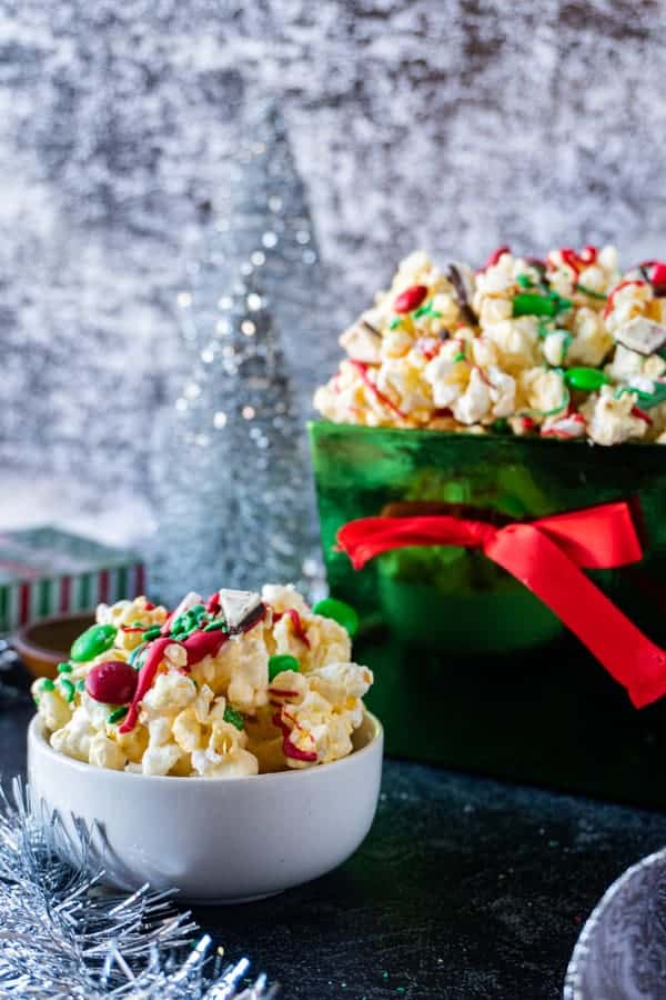 Christmas Popcorn in a small bowl next to a larger Christmas bowl