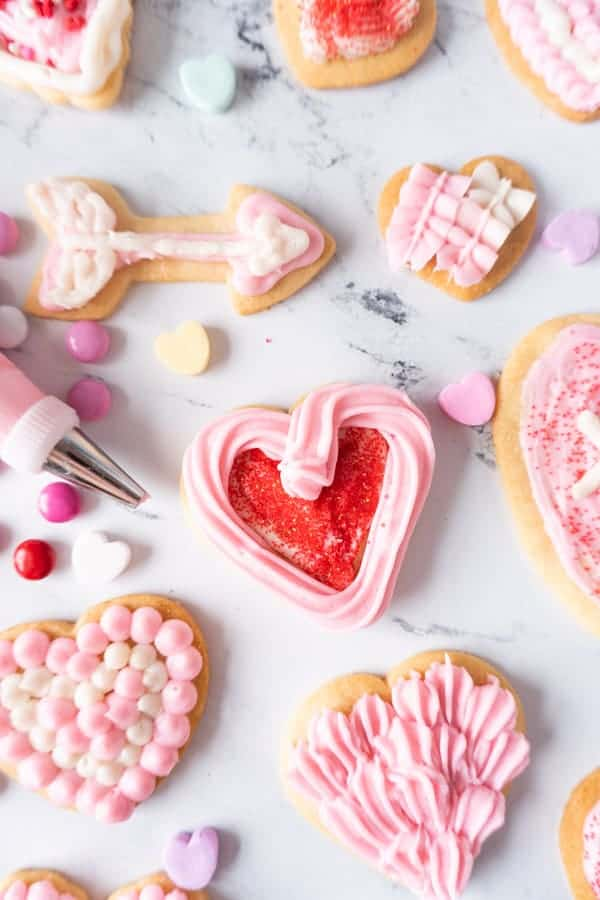 Valentine's Sugar Cookies decorated with different sprinkles and pink frosting