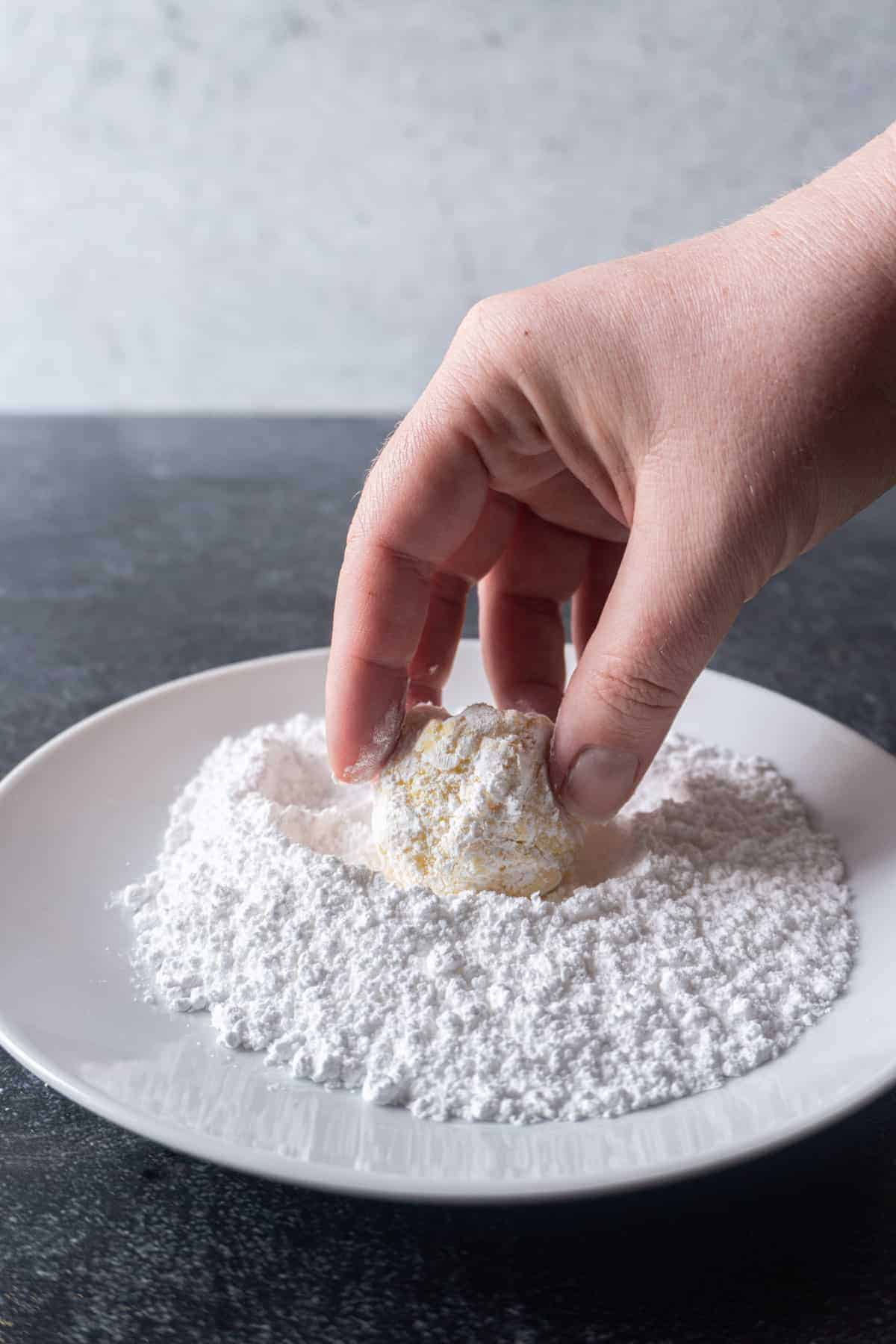 Cookie dough being rolled in powdered sugar